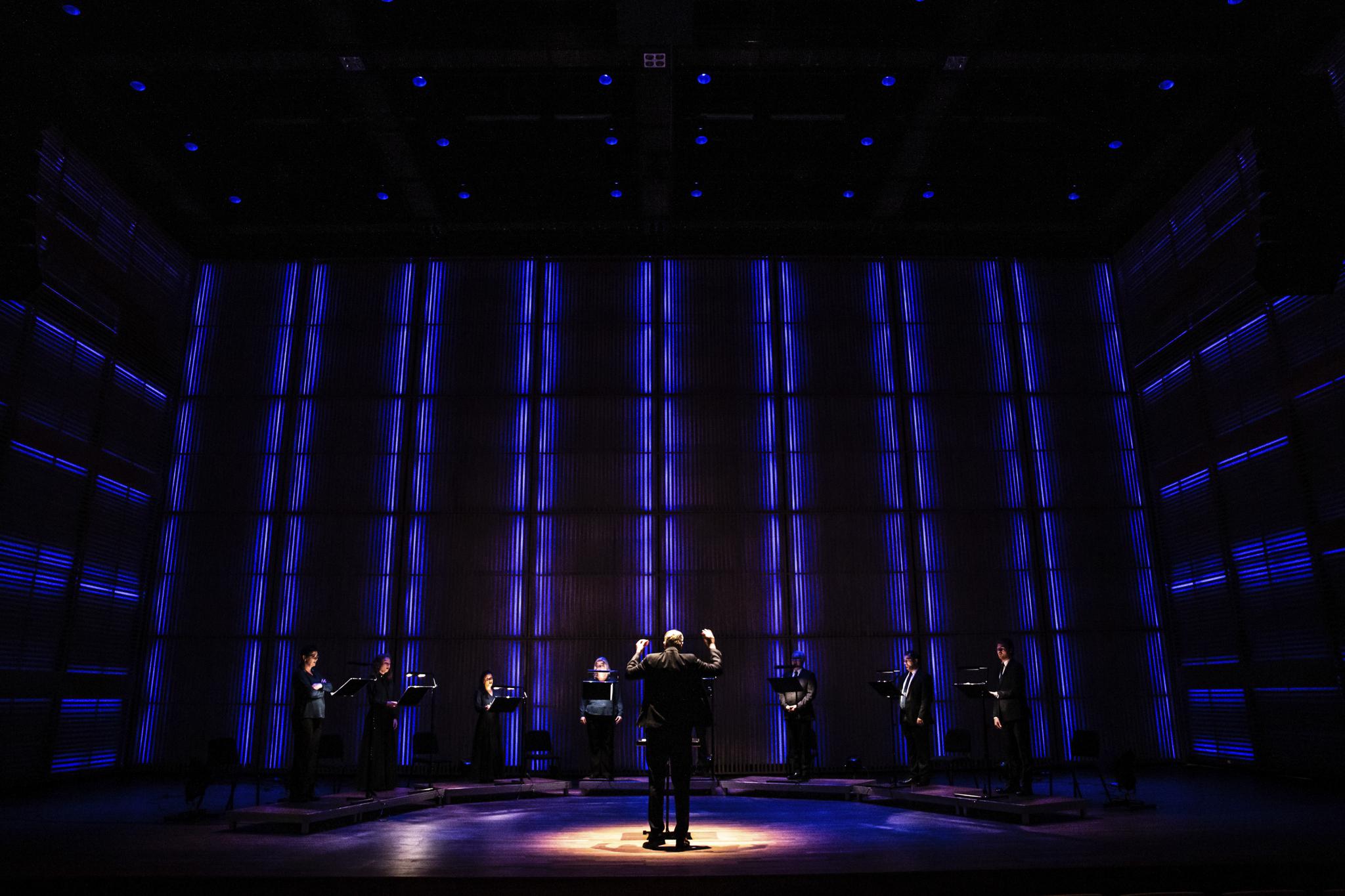 Melle Meivogel, Nizozemska: Svetloba v temi, 2020, prvi nastop Nizozemskega komornega pevskega zbora po zaprtju zaradi covida-19, Nizozemska - Fotografija prikazuje prvi nastop Nizozemskega komornega pevskega zbora po razglasitvi karantene v državi leta 2020. Naslov koncerta je bil Svetloba v temi. Nastop se je začel v popolni temi, svetloba pa je počasi začela osvetljevati oder kot simbol upanja za prihodnost zborovskega petja.