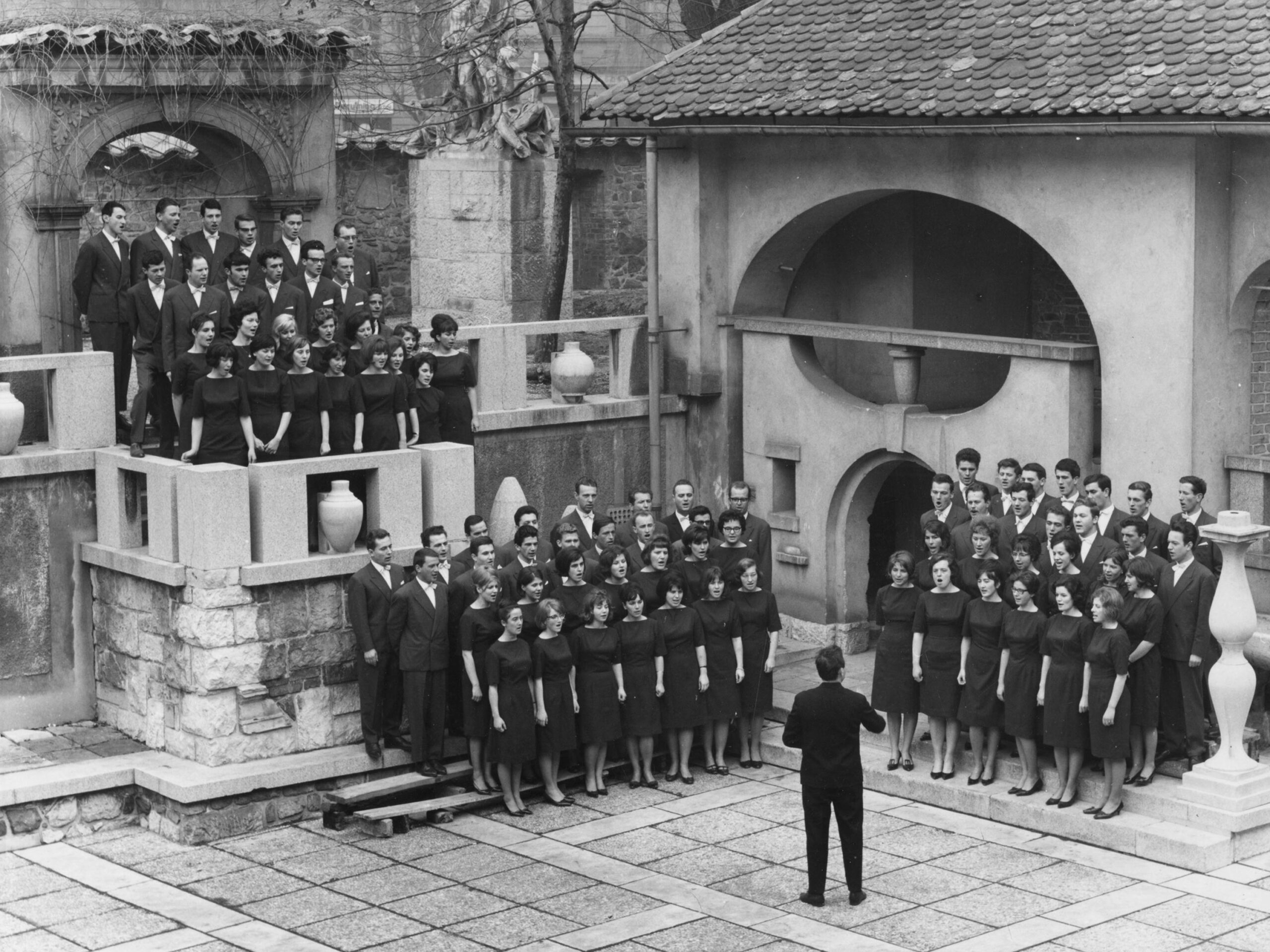 Archives of the Academic Choir Tone Tomšič of the University of Ljubljana, Slovenia: Academic Choir Tone Tomšič and Lojze Lebič, Slovenia - In 1961, composer, conductor, pedagogue and academic writer Lojze Lebič took over the leadership of the famous Academic Choir Tone Tomšič from Ljubljana. The photograph depicts the choir while performing at the Križanke Summer Theatre sometime between 1960 and 1970.